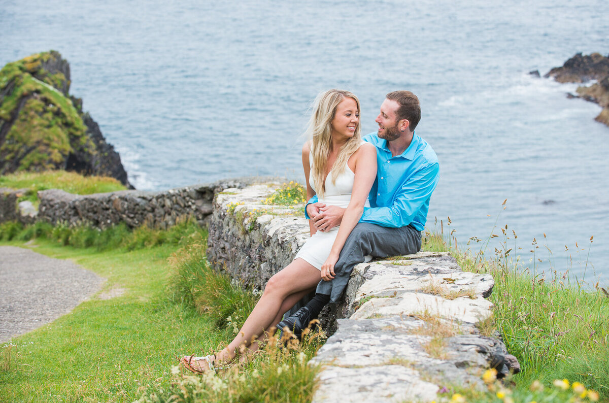 Engagement portrait of young couple sitting on a natural stone wall in Dunquin