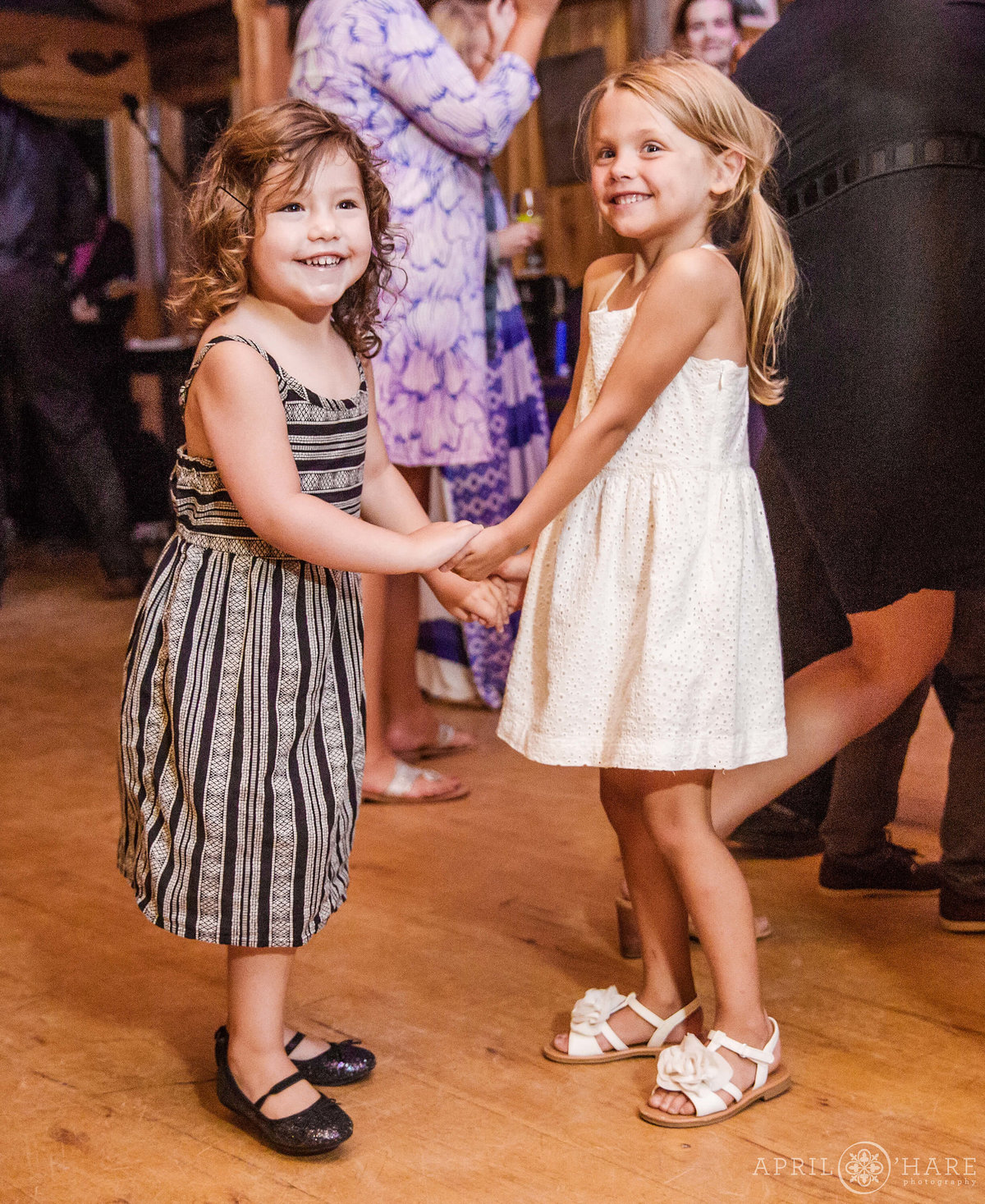 Sweet wedding photo of flower girls dancing at Reception in Colorado Mountains