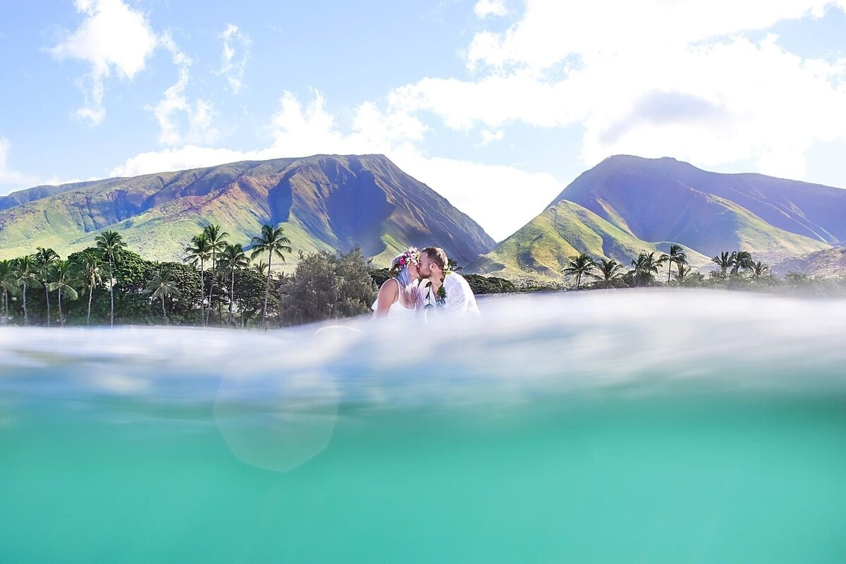 Bride and groom kiss on surfboards in the water with West Maui Mountains in the backdrop