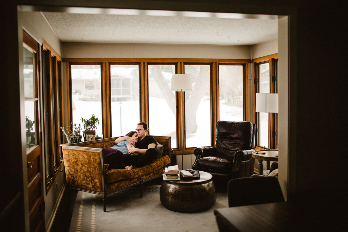 husband and wife snuggle on couch in sunroom
