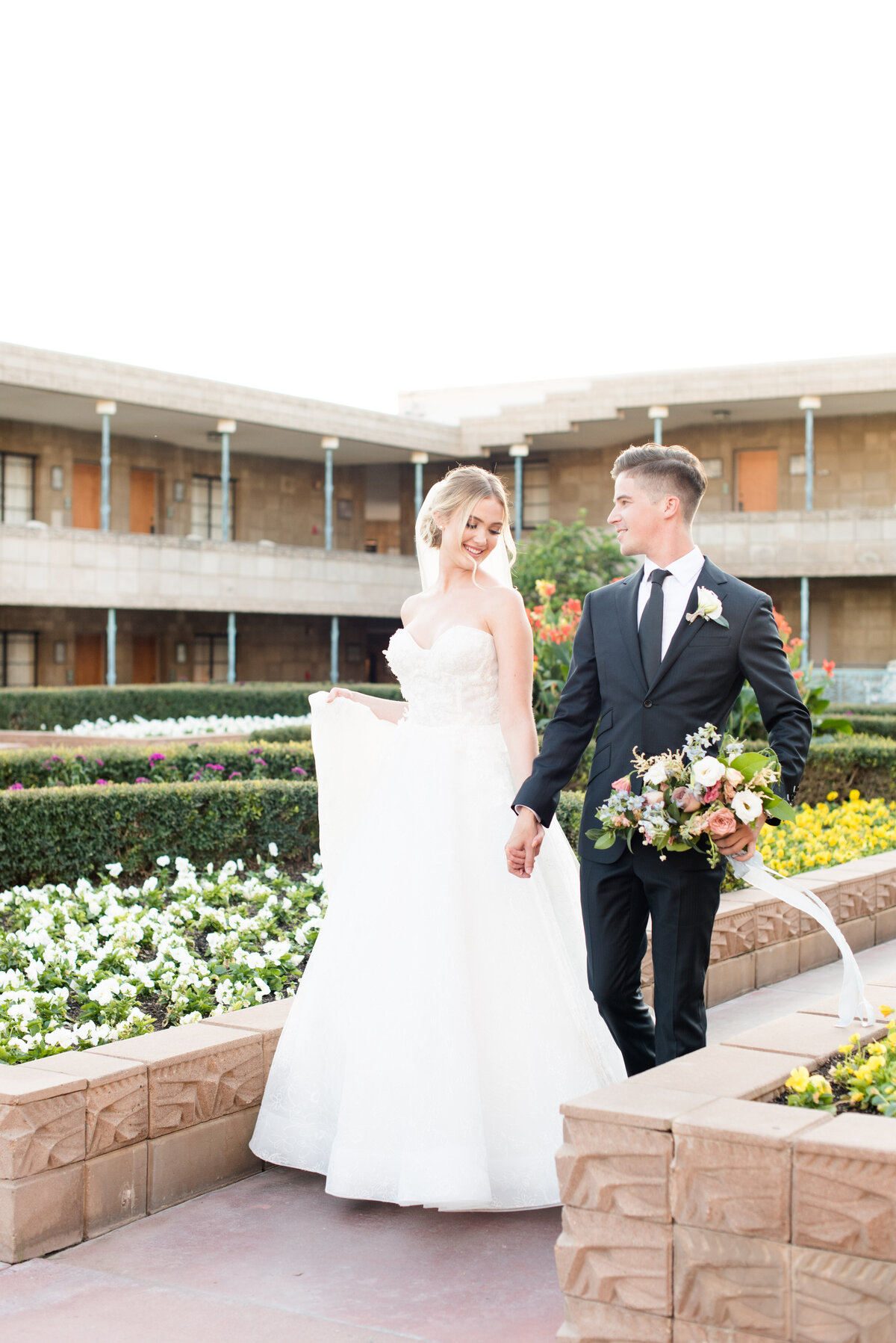A groom leads his bride through the garden at the Arizona Biltmore Hotel
