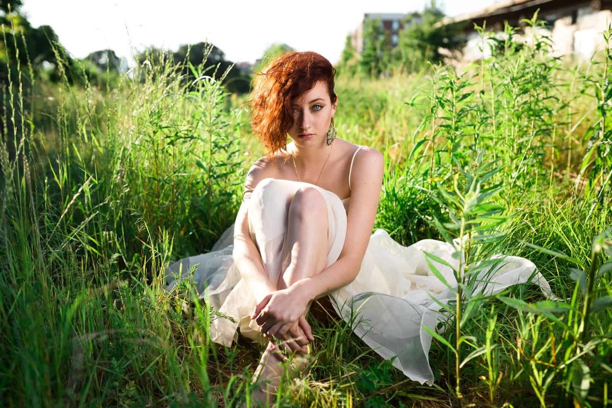 redhead girl in white dress sits in grass field of Atlanta Beltline