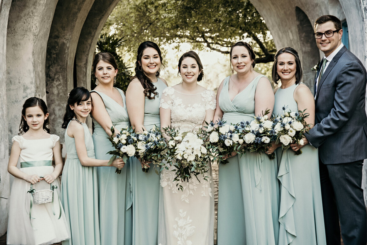 A photograph of a bride with her bridesmaids, flower girls, and friend, holding their bouquets and smiling as they are lined up in their beautiful dresses by Garry & Stacy Photography Co - St Petersburg wedding photography