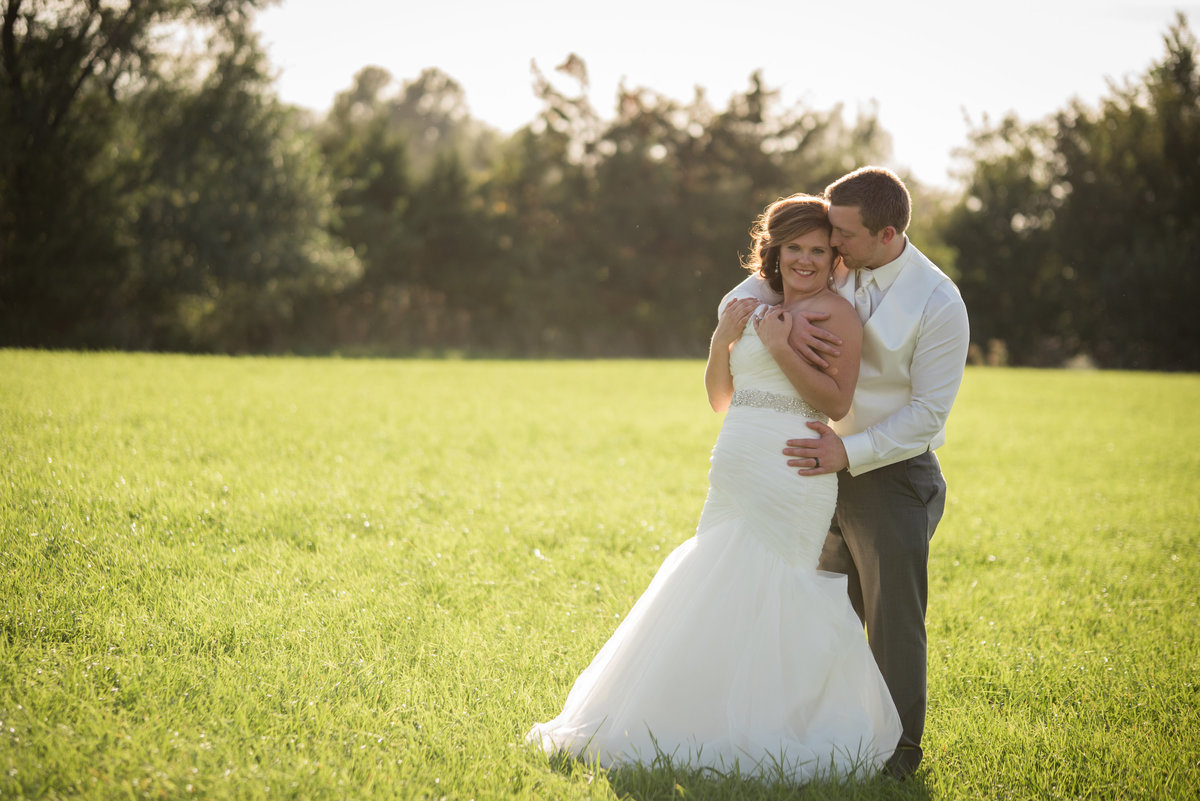 bride and groom holding eachother in open field