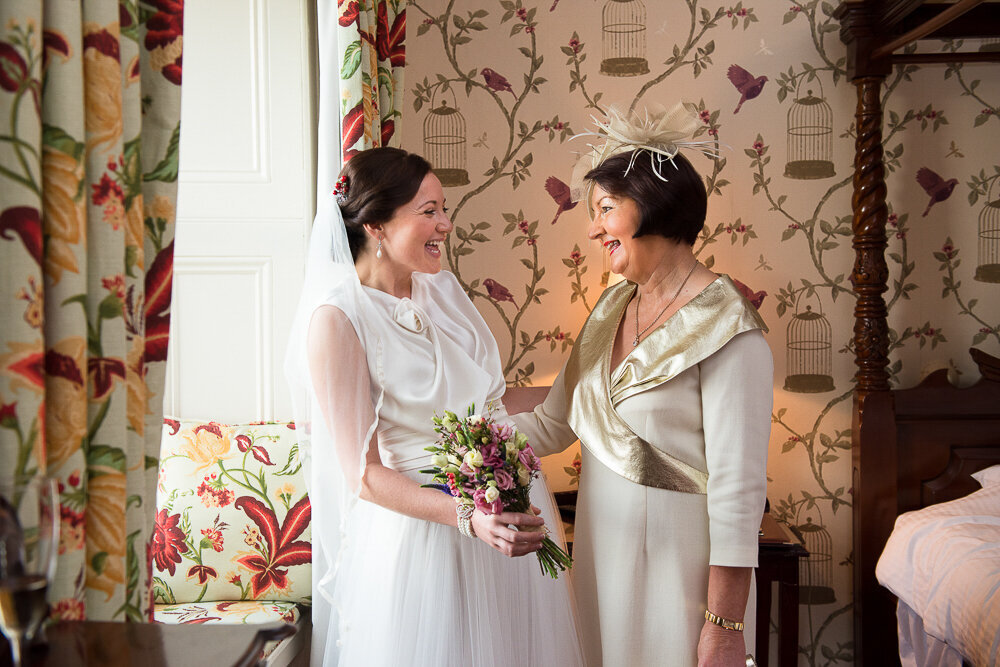 bride wearing an a-line silk and tulle wedding dress looking at her mother wearing a cream dress while standing in the bridal suite of Ballyseede Castle