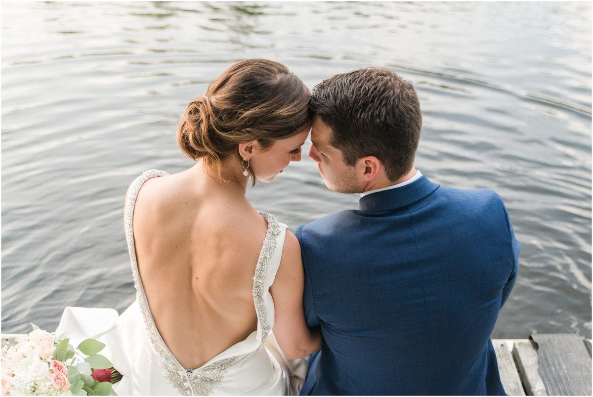 Bride and groom sitting on a dock putting their feet in the water