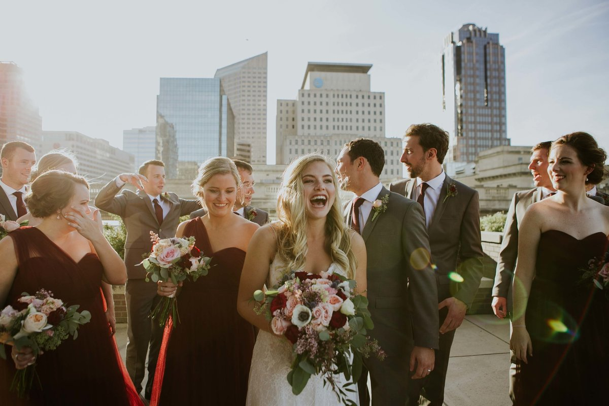 Couple and wedding party walk on top of roof top of Regions tower wedding