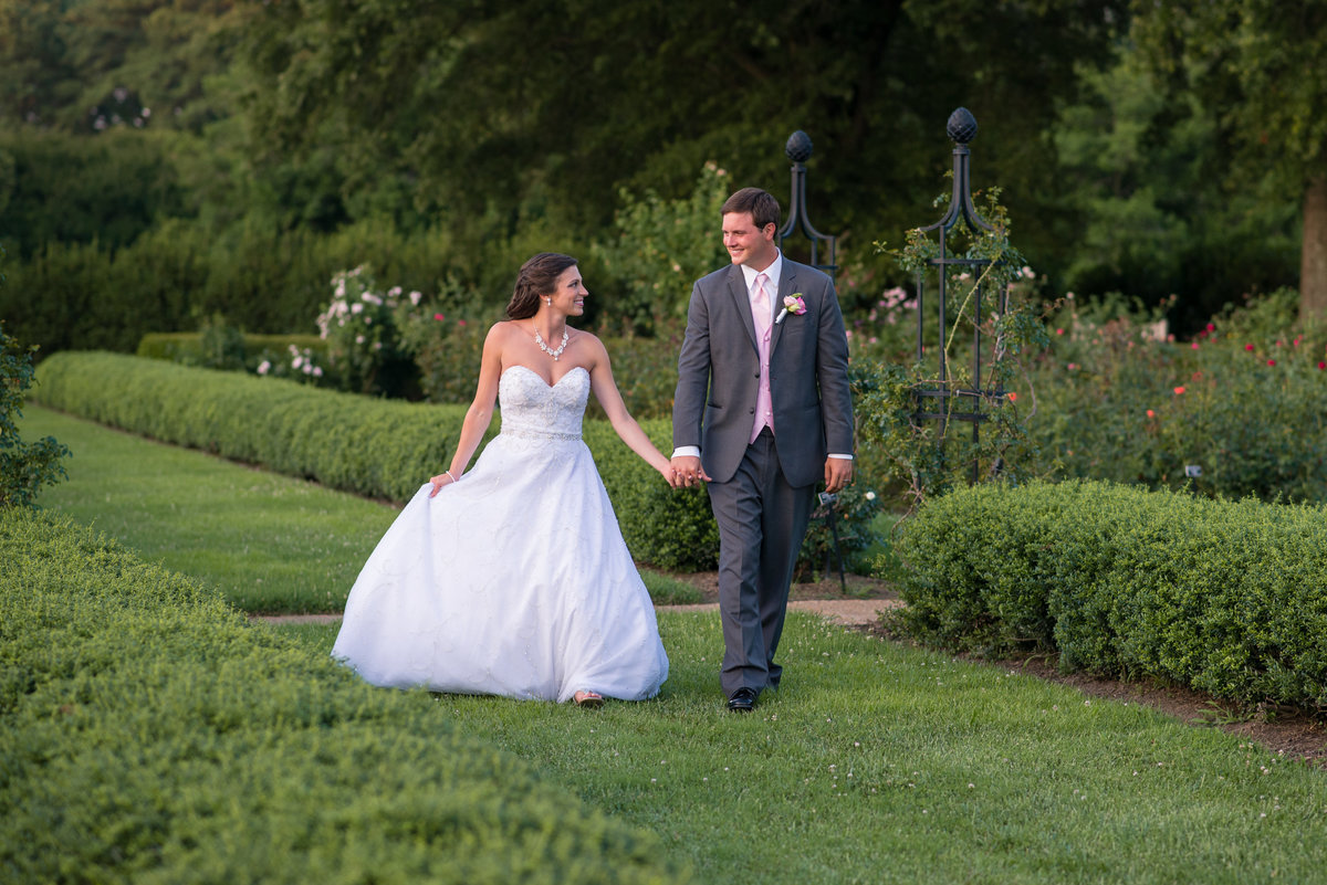 Bride and groom walking in the rose garden at Norfolk Botanical Garden