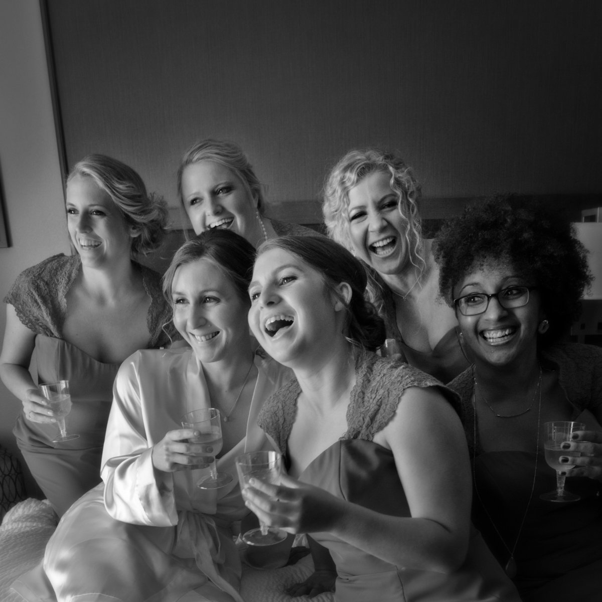 Black and White of Bride and Bridal Party drinking champagne in Bridal Suite