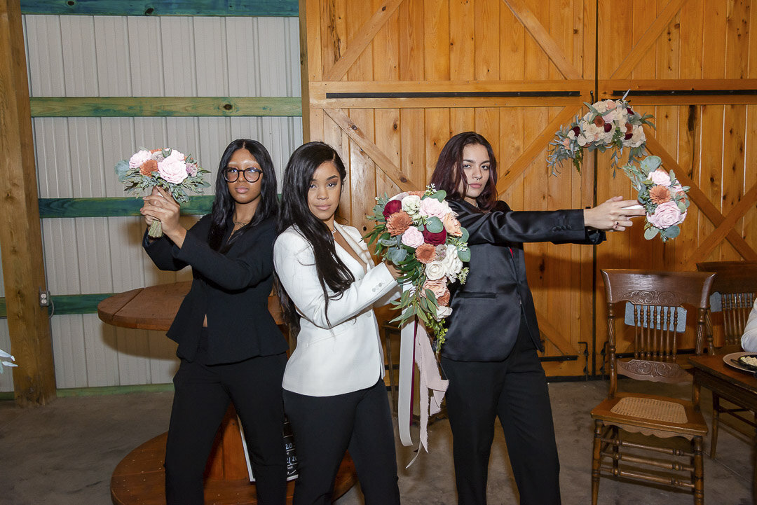 Bride and her bridesmaids pose like Charlie's Angels with their bouquets.