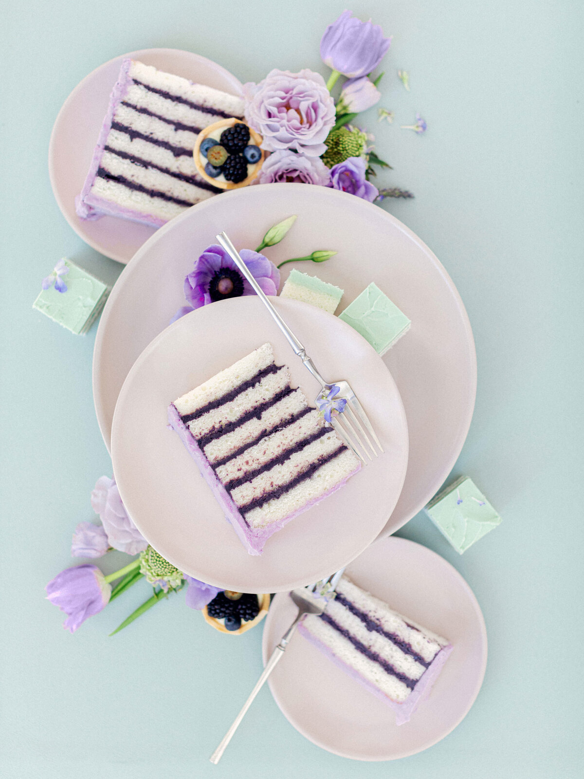 purple cake slices laying on plates surrounded by purple florals against green background wedding flat lay