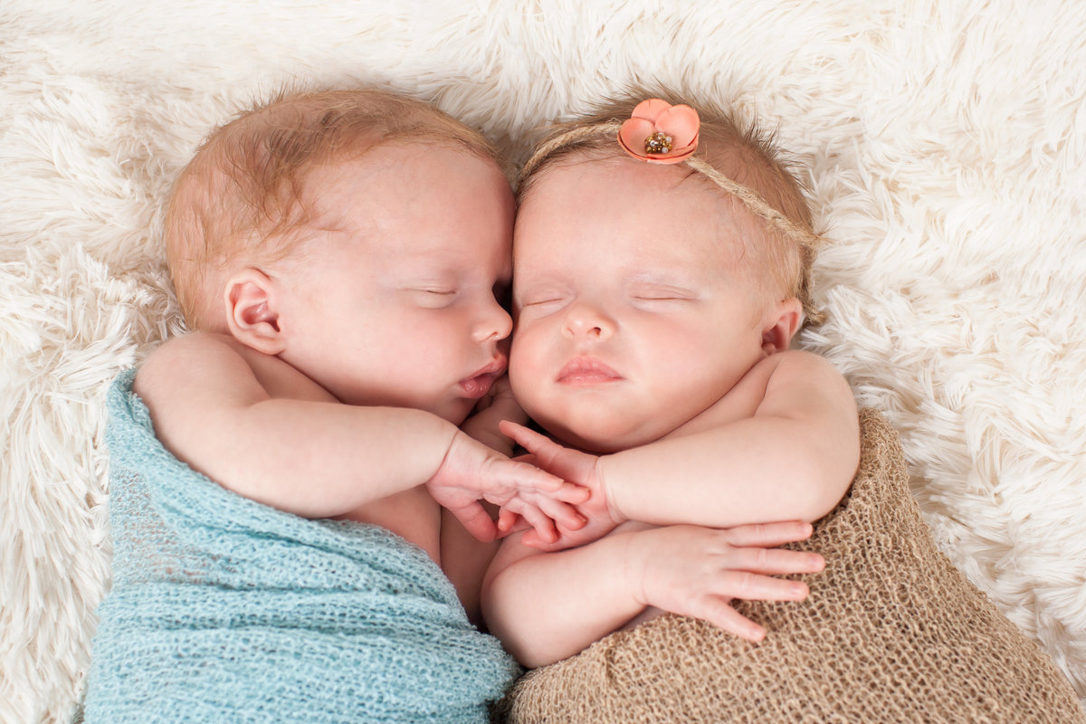 Twin boy and girl sleeping on blanket