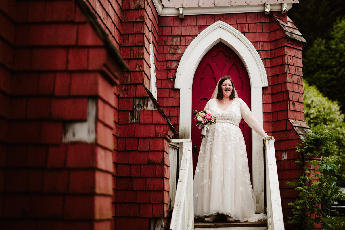 bride laughs on steps of st.peter's episcopal church in seward