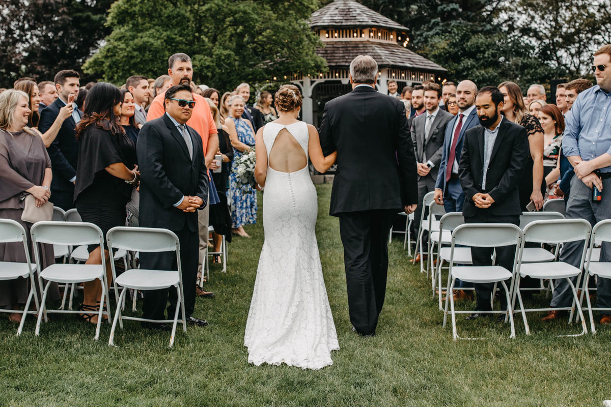 bride-and-dad-walking-down-asile-wedding-ceremony-ruffled-feathers-golf-club-lemont-il-adventurous-wedding-photographer-4