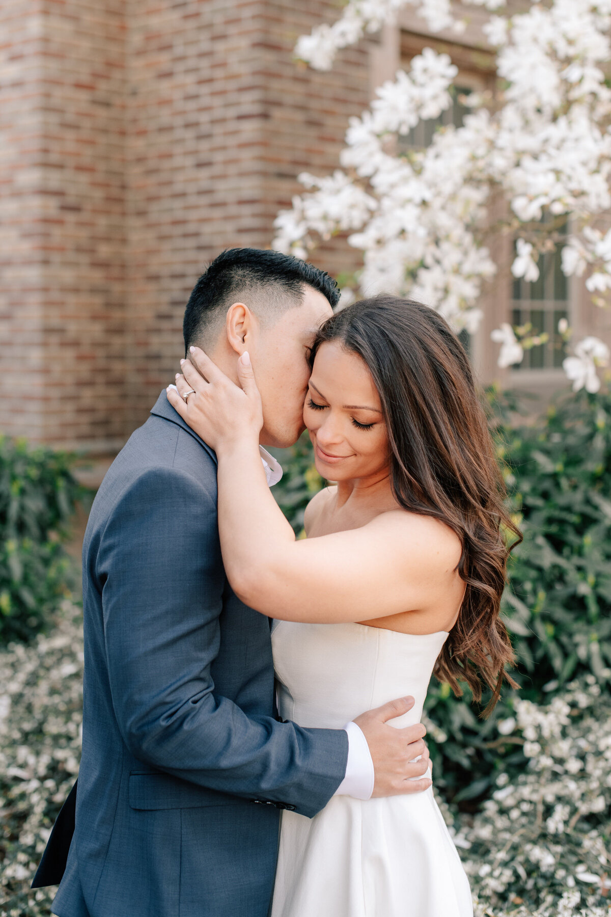 Groom kissing bride during cherry blossom engagement at UW