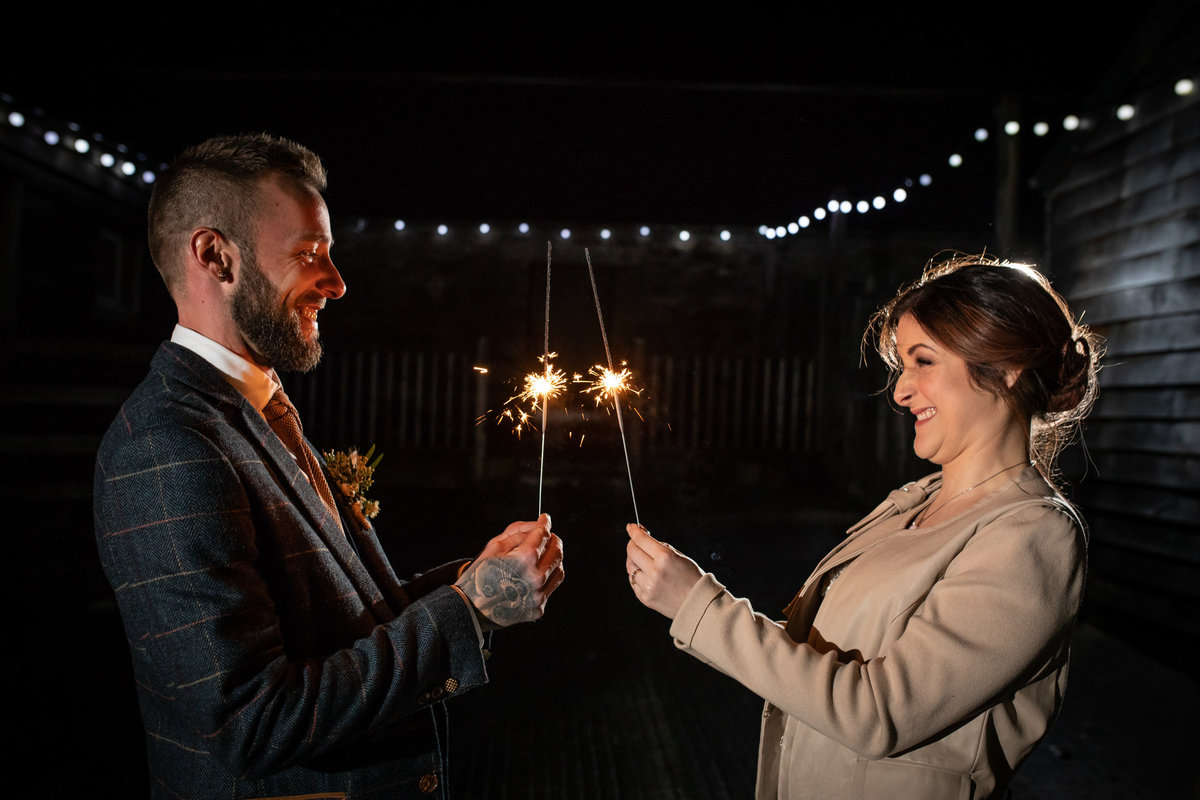 Newly married couple with sparklers at The Green in Cornwall