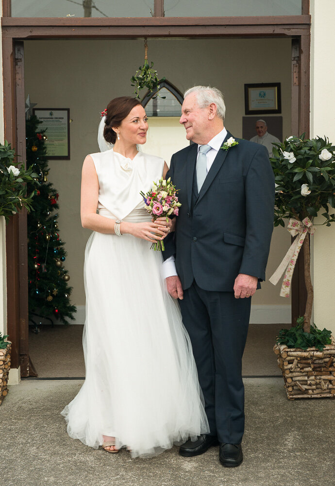 brunette bride wearing an a-line, satin and tulle wedding dress standing at the church door with her dad who is wearing a dark nay suit