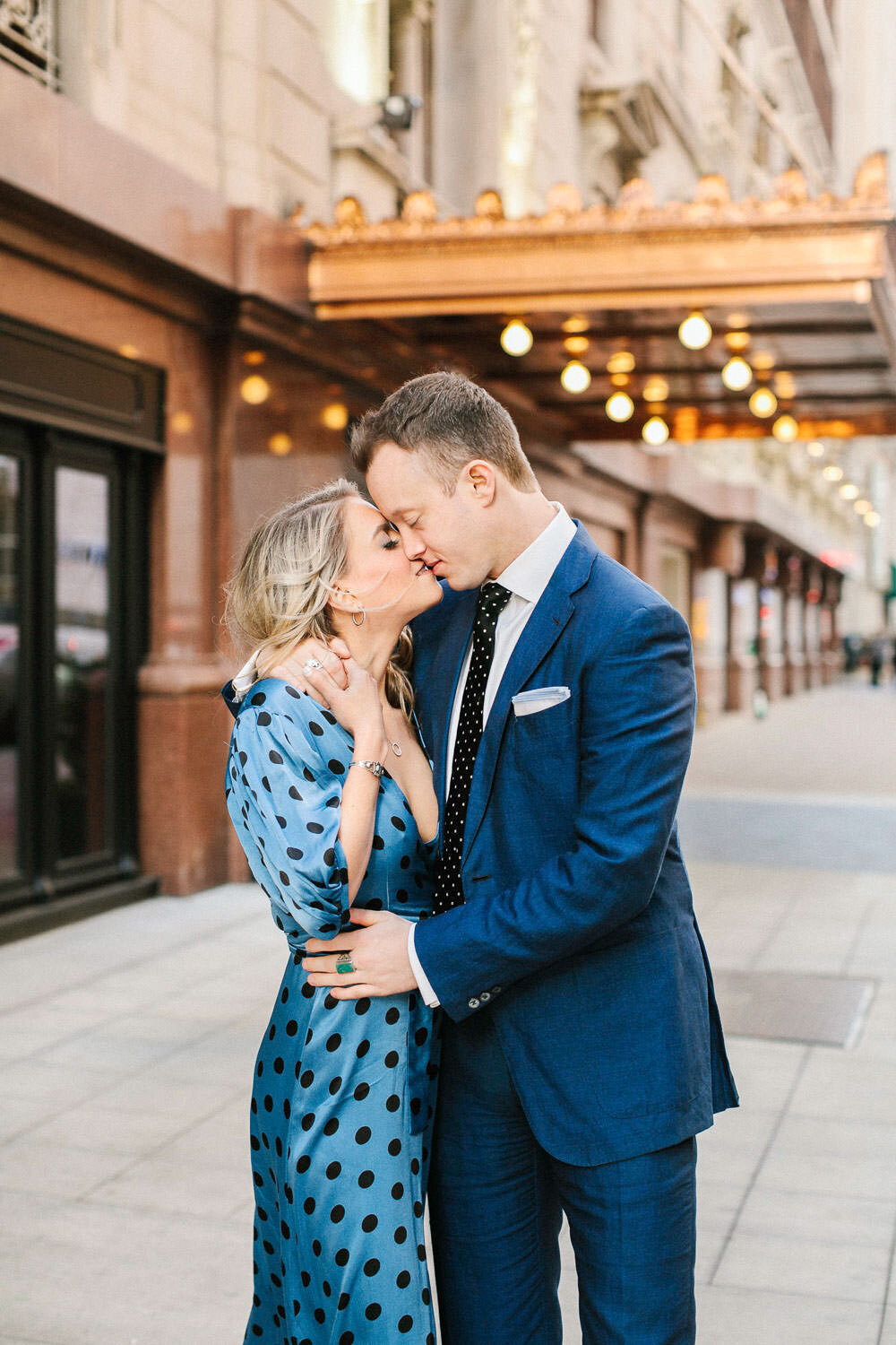 Girls in blue polkadot dress kissing man in blue suit on street corner