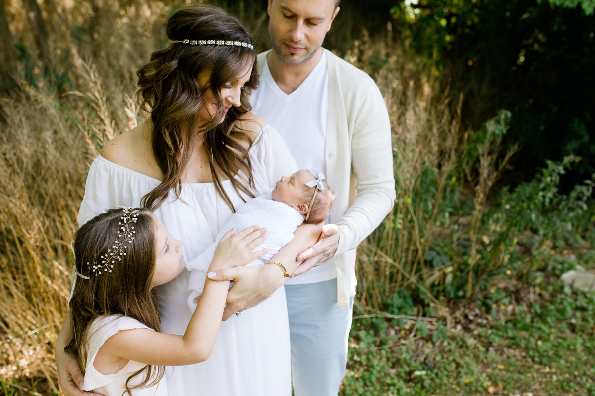 Family of four looking down and holding newborn baby girl {Oakville Family Photographer}