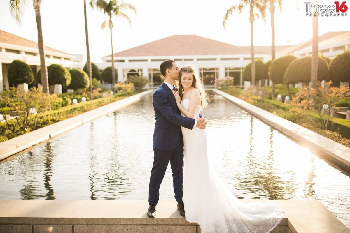 Groom embraces his Bride while standing on the wall surrounding the reflection pool at the Richard Nixon Library