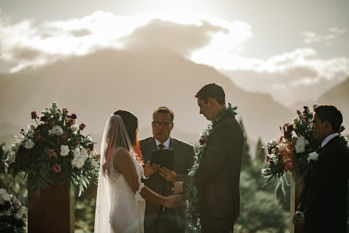 Bride-and-groom-hold-hands-during-wedding-ceremony-overlooking-the-mountains