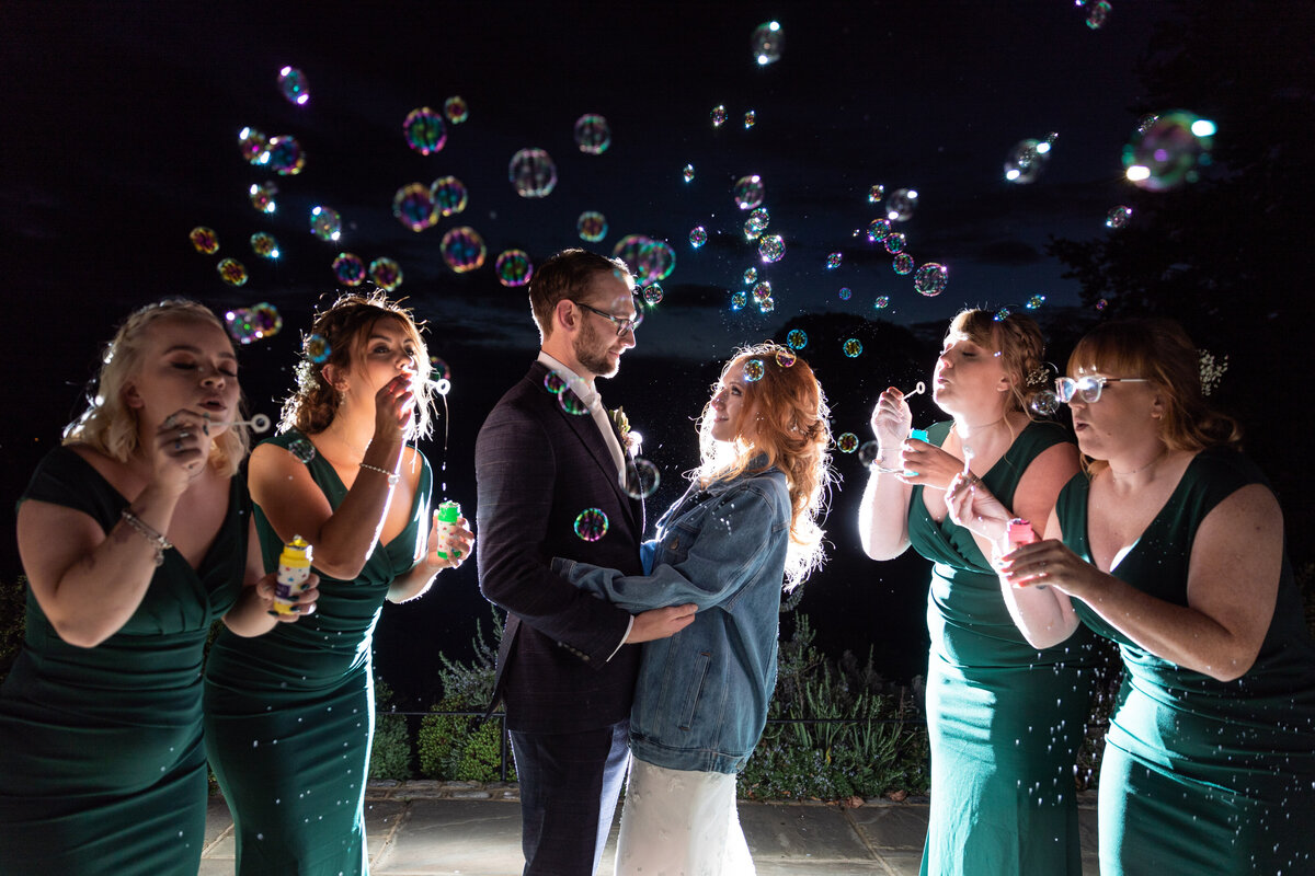 A Bride and Groom surrounded by their Bridesmaids blowing bubbles