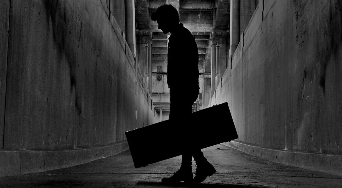 Musician portrait Los Angeles black and white image lead singer standing in tunnel in silhouette holding guitar case