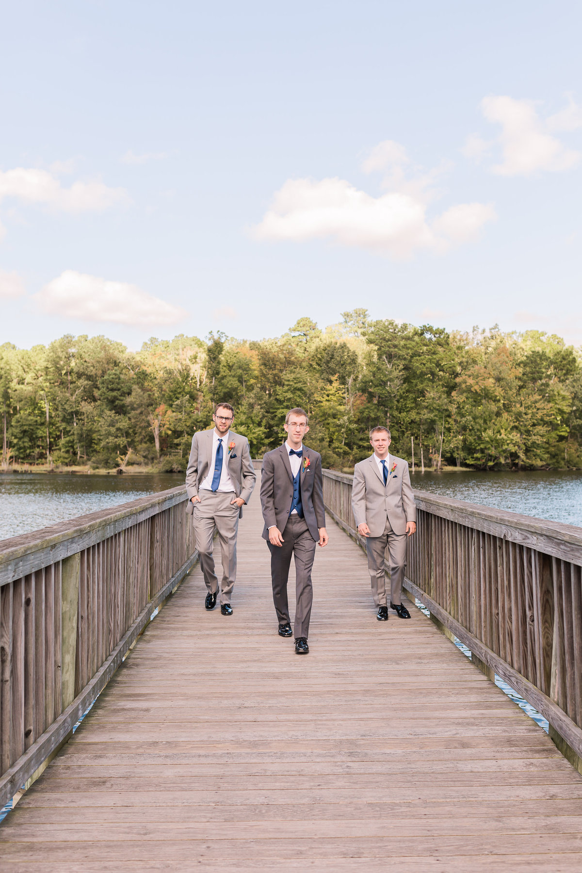A groom and his groomsmen walk down the boardwalk at Newport News Park