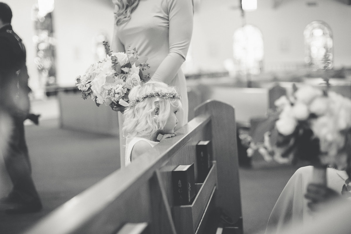 A Flower Girl Rests Her Head on the Back of a Pew While Waiting for a Saint Augustine Wedding to Begin
