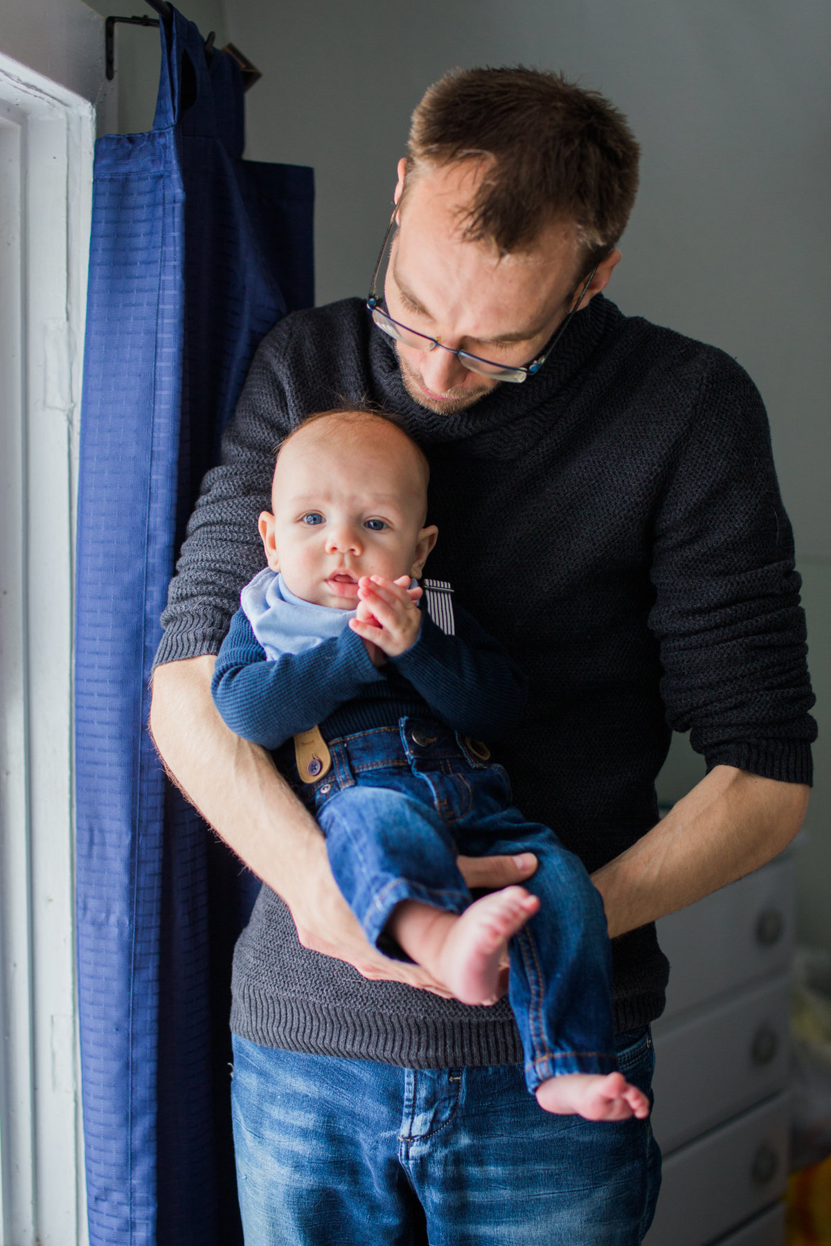Dad holding baby by window during newborn session with Jennifer Blaak Photography
