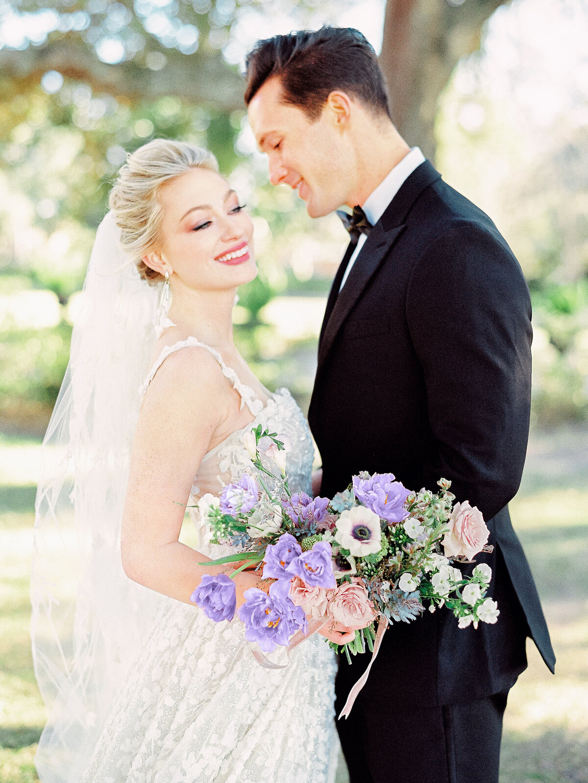 Bride and groom embracing with purple floral bouquet laughing outside wedding Charleston