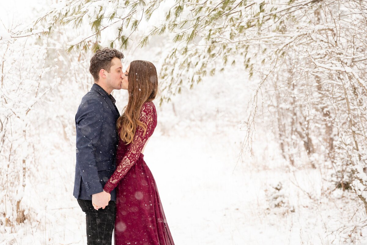 Couple-dresses-up-for-their-engagment-session-and-share-a-kiss-as-the-snow-falls-during-their-winter-engagement-session-at-Sydenham-ridge