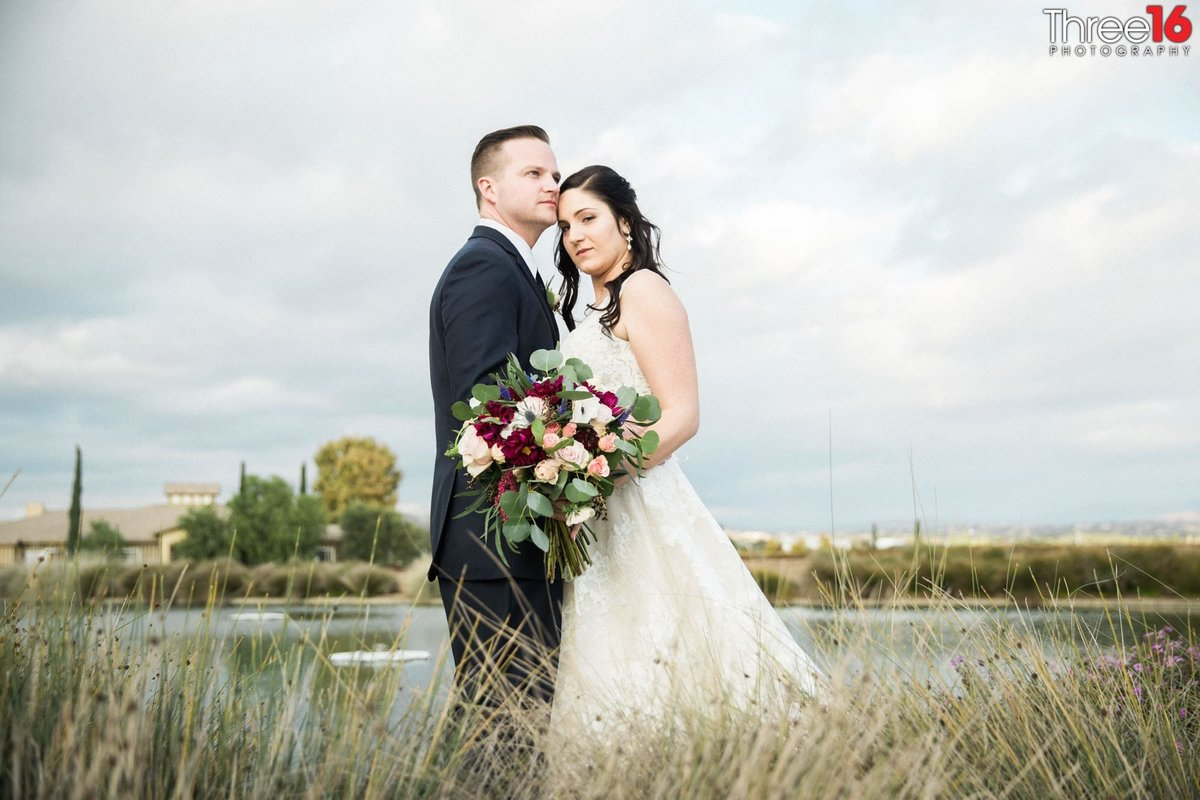 Bride and Groom share intimate moment together in an open field