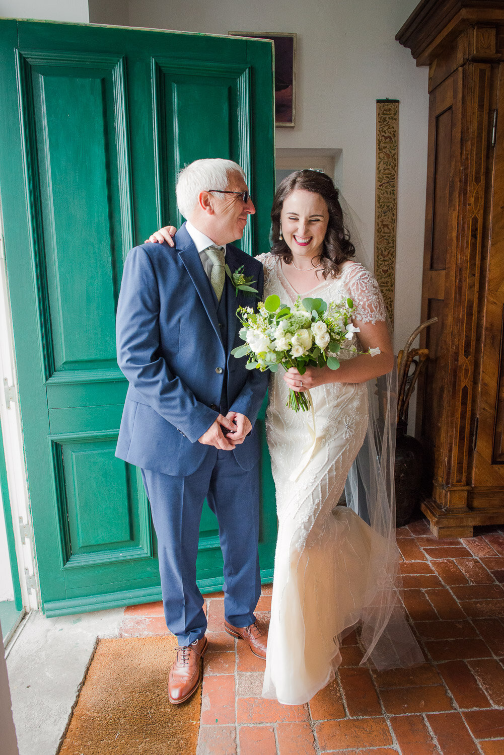 brunette bride in vintage, beaded wedding dress sharing a moment with her father in law at the door of Westcove House