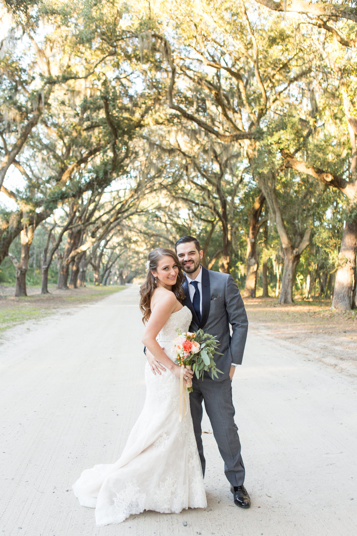 bride and groom holding each other under oaks at wormsloe