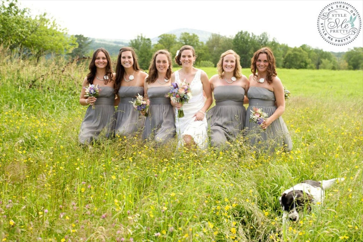 fun and candid wedding photo of bridesmaids in the fields with dog