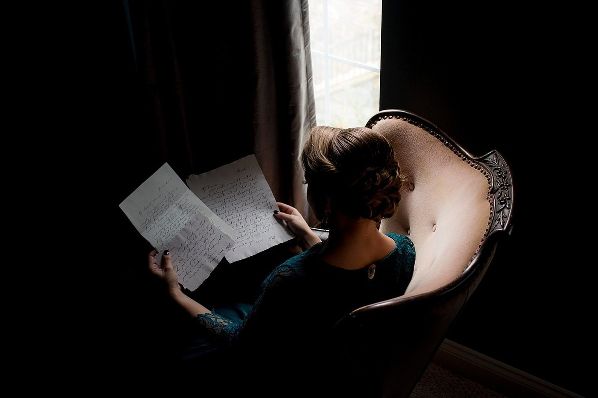 Dark and Moody Bridal Portrait of Bride Reading Love Letter