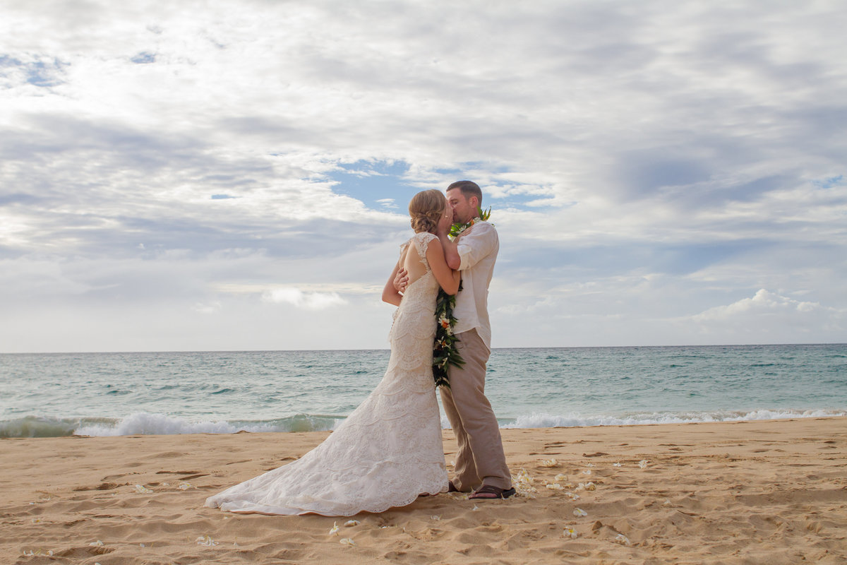 Couples first married kiss at the beach on Kauai.