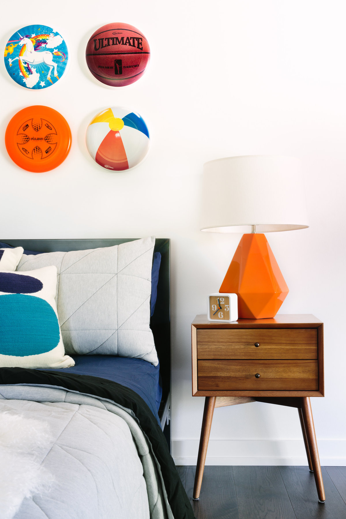 Boys bedroom with walnut nightstand, orange lamp, and frisbee art installation