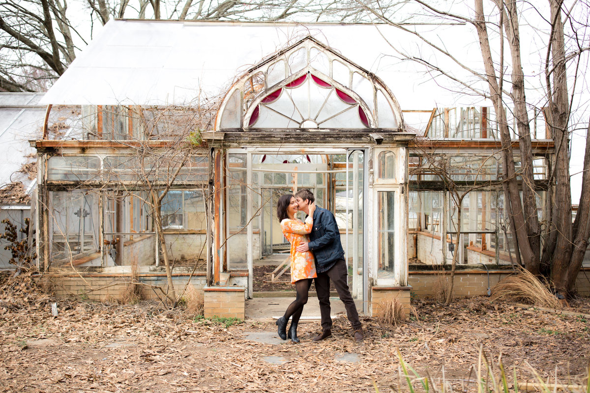trendy couple kissing outside of Briarcliff mansion greenhouse in Atlanta georgia for wedding photographer