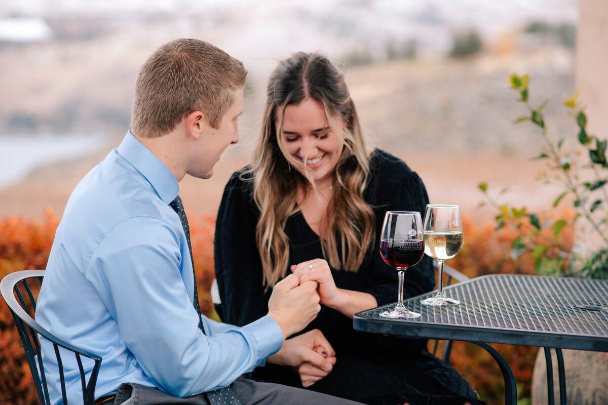 Couple drinking wine and looking at engagement ring after surprise proposal at Benson Vineyards