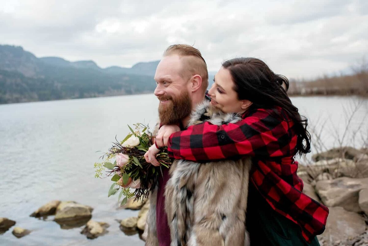 a woman hugs behind her fiance as they overlook the columbia river at dalton point