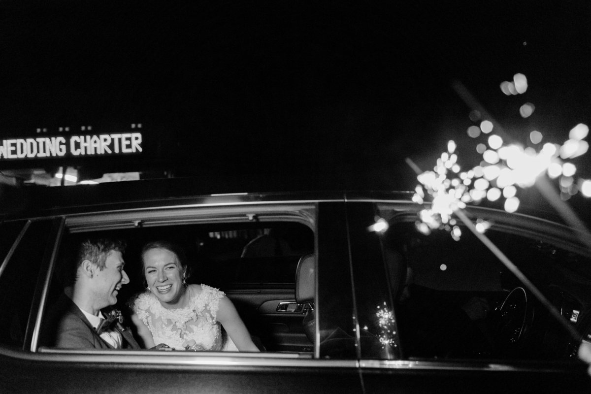 bride and groom laugh in wedding getaway car
