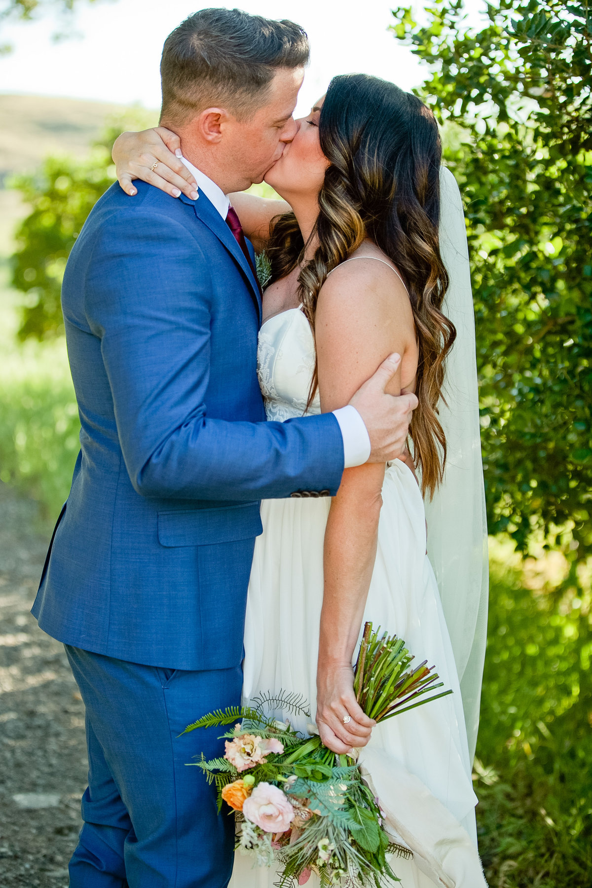 Romantic Spring Elopement  bride and groom in kissing with Spring bouquet at Higuera Ranch  in San Luis Obispo  by Amy Britton Photography Photographer in St. Louis