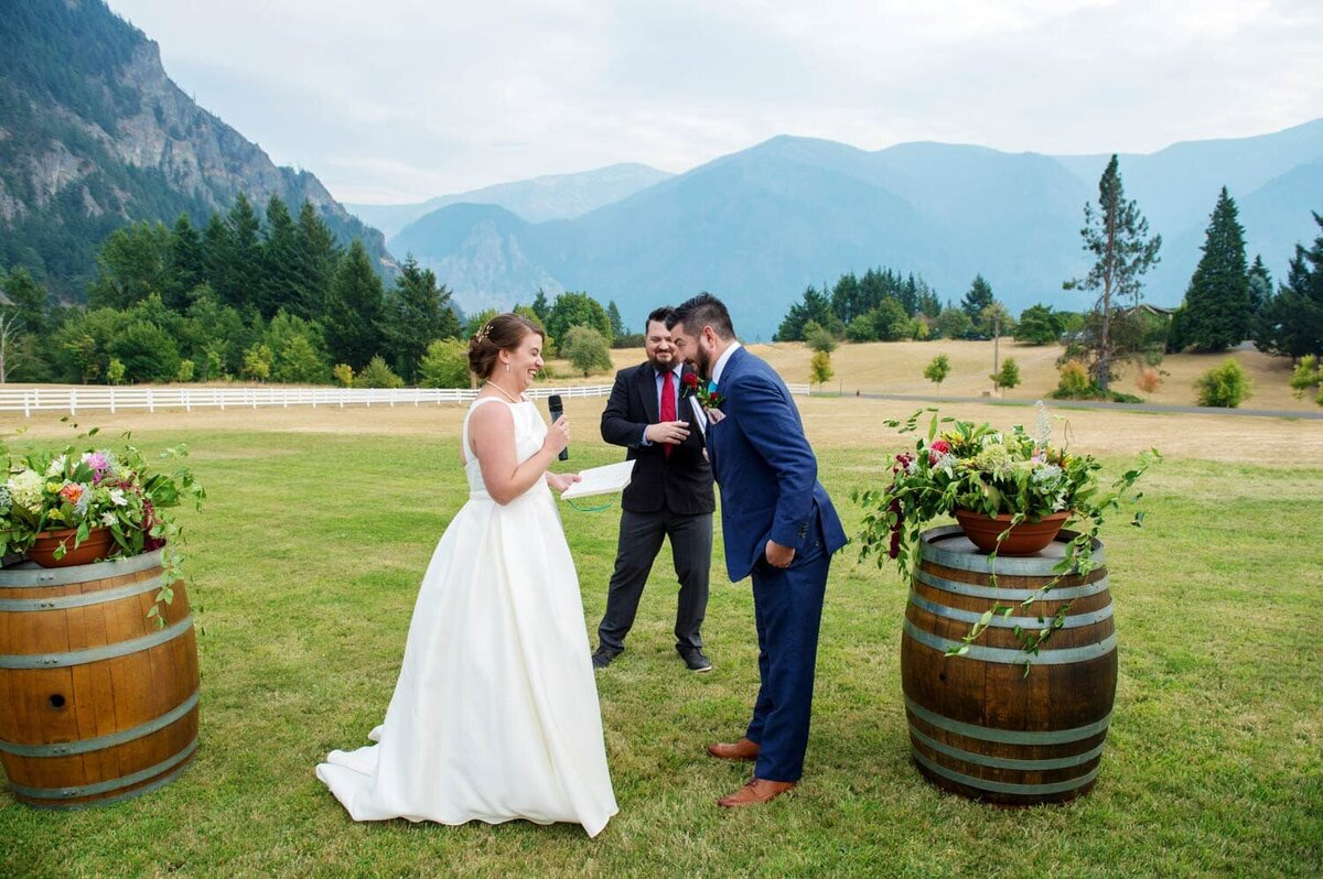 a couple share a silly moment during their wedding vows at wind mountain ranch