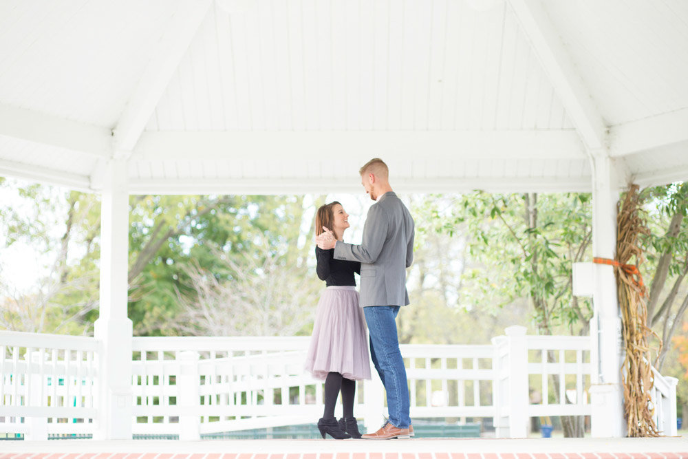 Engaged couple dancing under gazebo