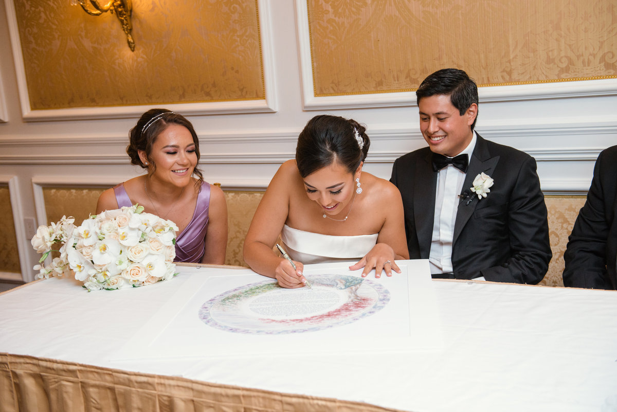 photo of bride signing the ketubah aside her groom and bridesmaid from wedding at The Garden City Hotel