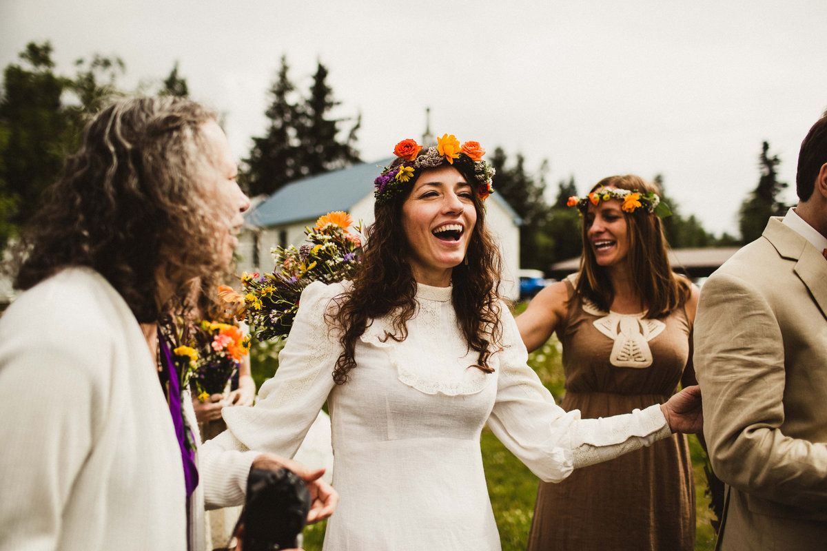 bride with colorful flower crown laughing at moose pass wedding