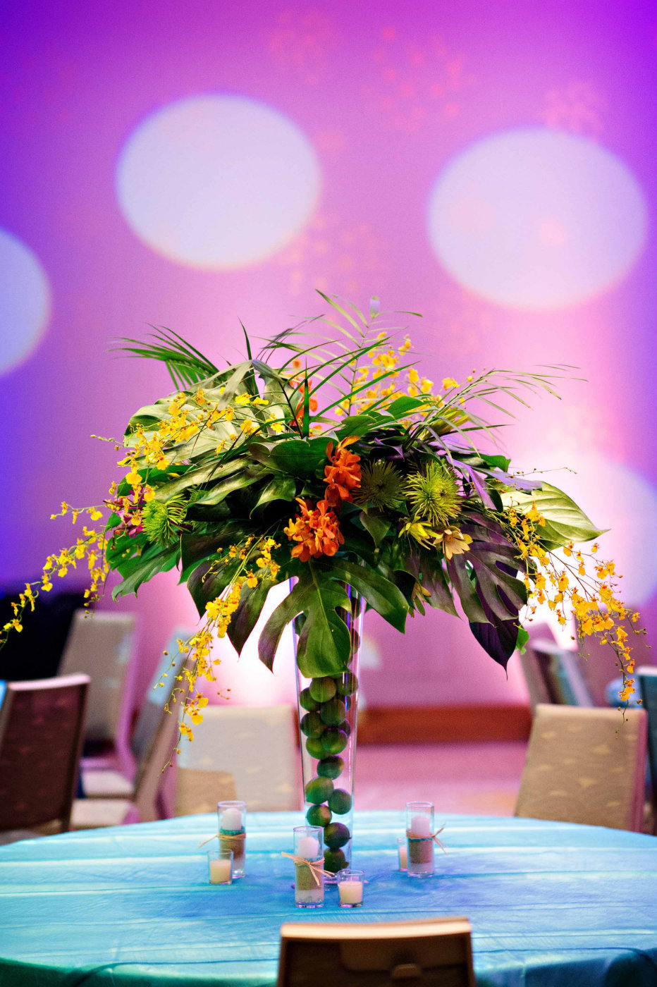 tall centerpiece with tropical leaves, purple orchids, in vase filled with limes on turquoise linen