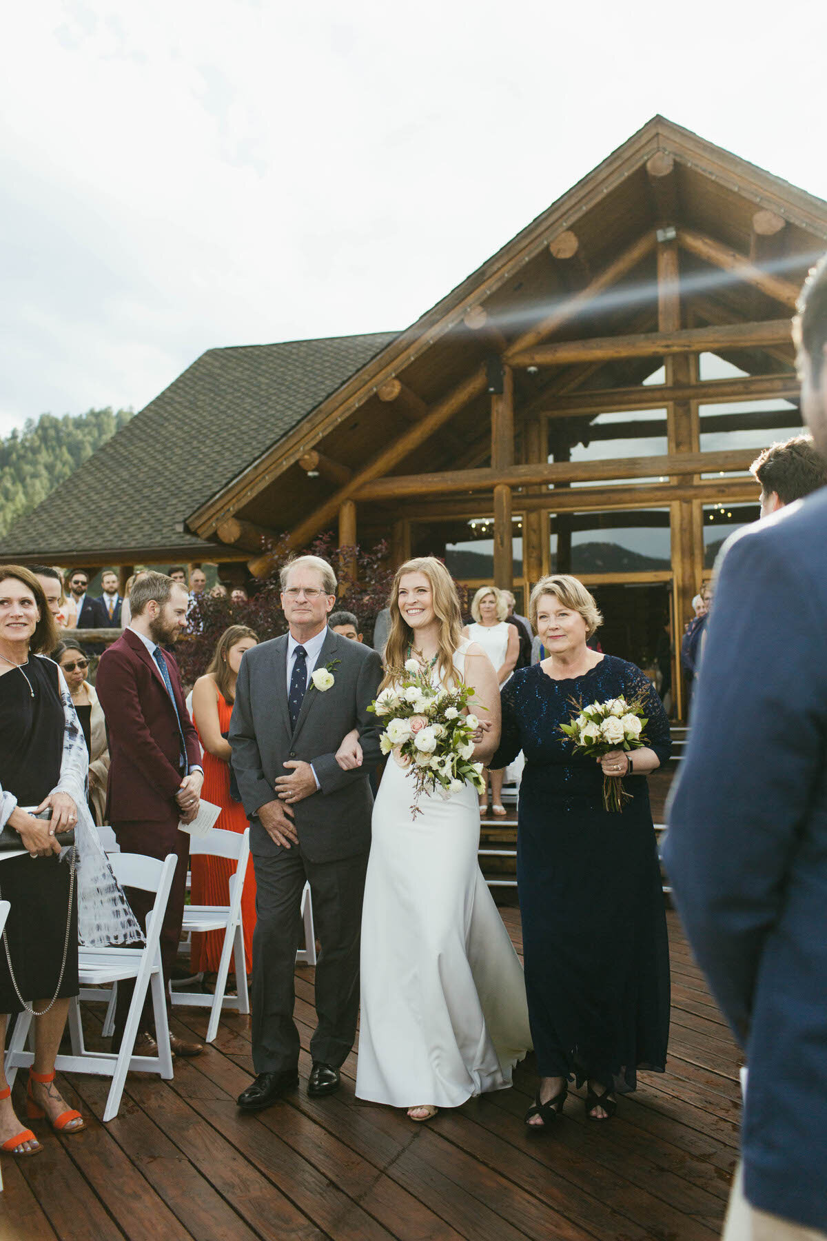 A man and woman walk the bride down the aisle in an outdoor wedding